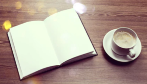 Open diary with blank pages sits on a wooden desk. A cup of coffee sits to the right.
