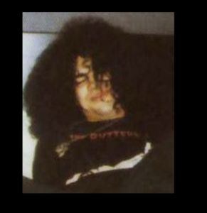 Drunk looking Slash wearing a Guttersluts t-shirt while laying down on a bed, cigarette in his mouth.